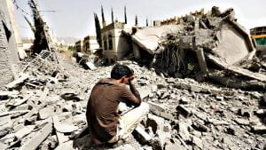 A young Yemeni man sits atop the rubble with his face in his palm grieving the destruction of his home