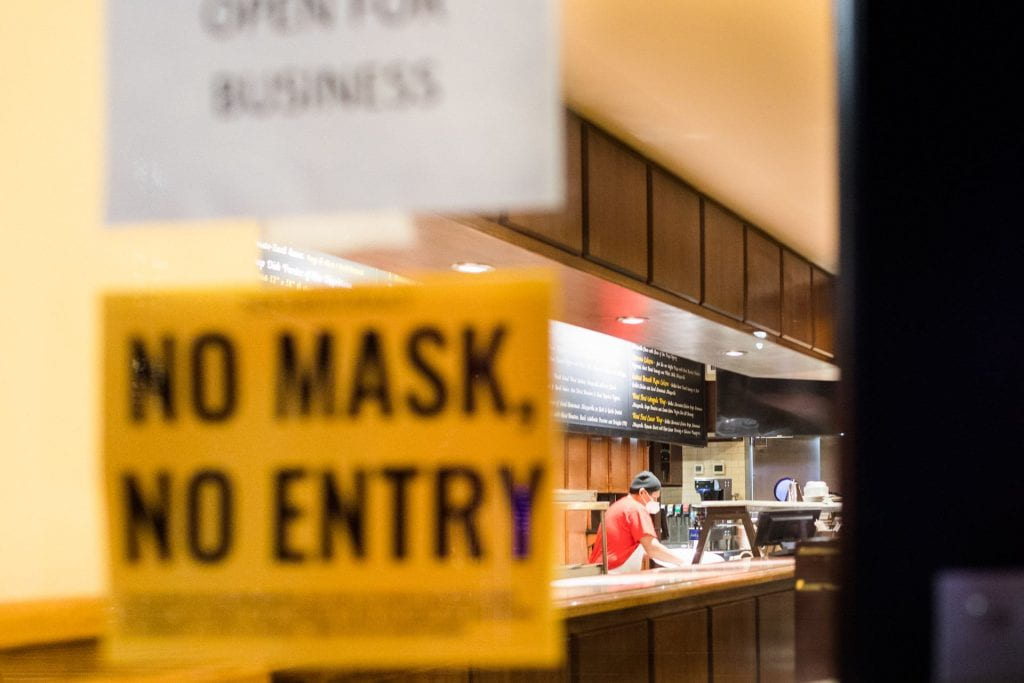 "Person with a protective mask preparing food with a front door sign that reads ""No Mask, No Entry""."