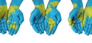 Three pairs of hands painted blue and green to represent the earth