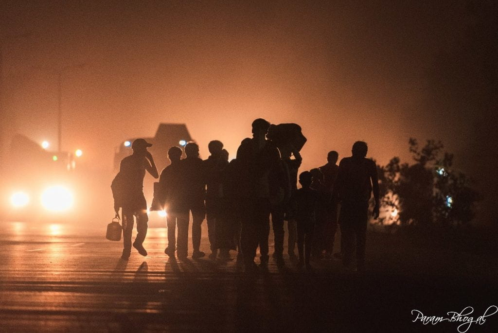 Migrant workers walking on the shoulder of a highway during the nighttime.