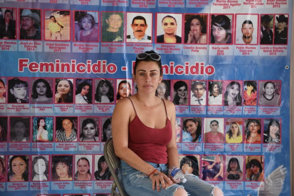 Woman sitting in front of a poster that includes pictures of femicide victims.