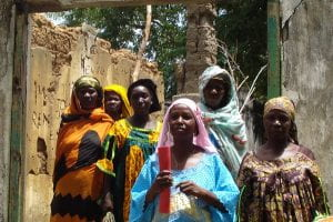African women dressed in colorful robes standing in an unfinished building. They are doing an inspection.