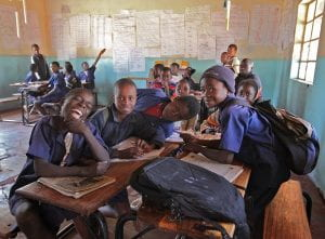 African school children in uniforms huddled around desks