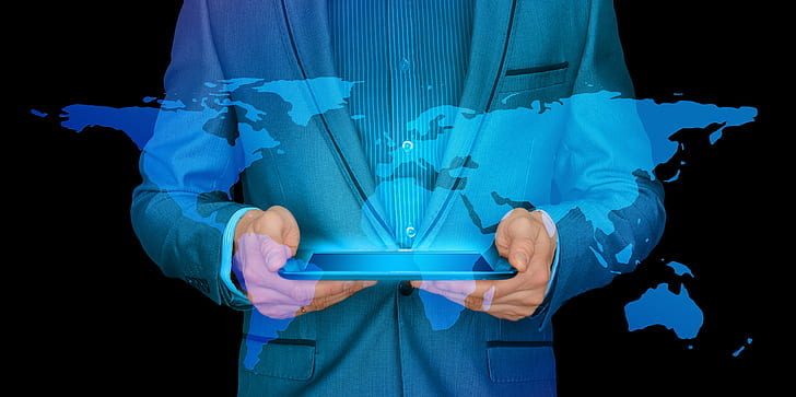 An image of a man in a blue suit holding a tablet with a hologram of the world map shining above.