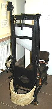 An image of a guillotine, with the blade and a basket where the head is supposed to be kept.