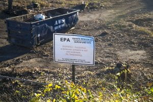 "dirt field with a dumpster and a sign that reads ""EPA Quanta Resources Superfund Site. Warning: Hazardous substances present in the soil. No trespassing."