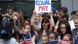 "Photo of a protest with woman holding sign that reads ""Equal Pay"""
