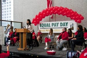"Image of woman speaking at conference with sign that reads ""Equal Pay Day"" in the background"