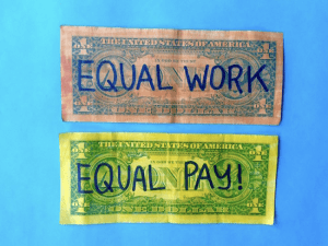 "Two dollars bills reading ""Equal Work"" and ""Equal Pay!"""