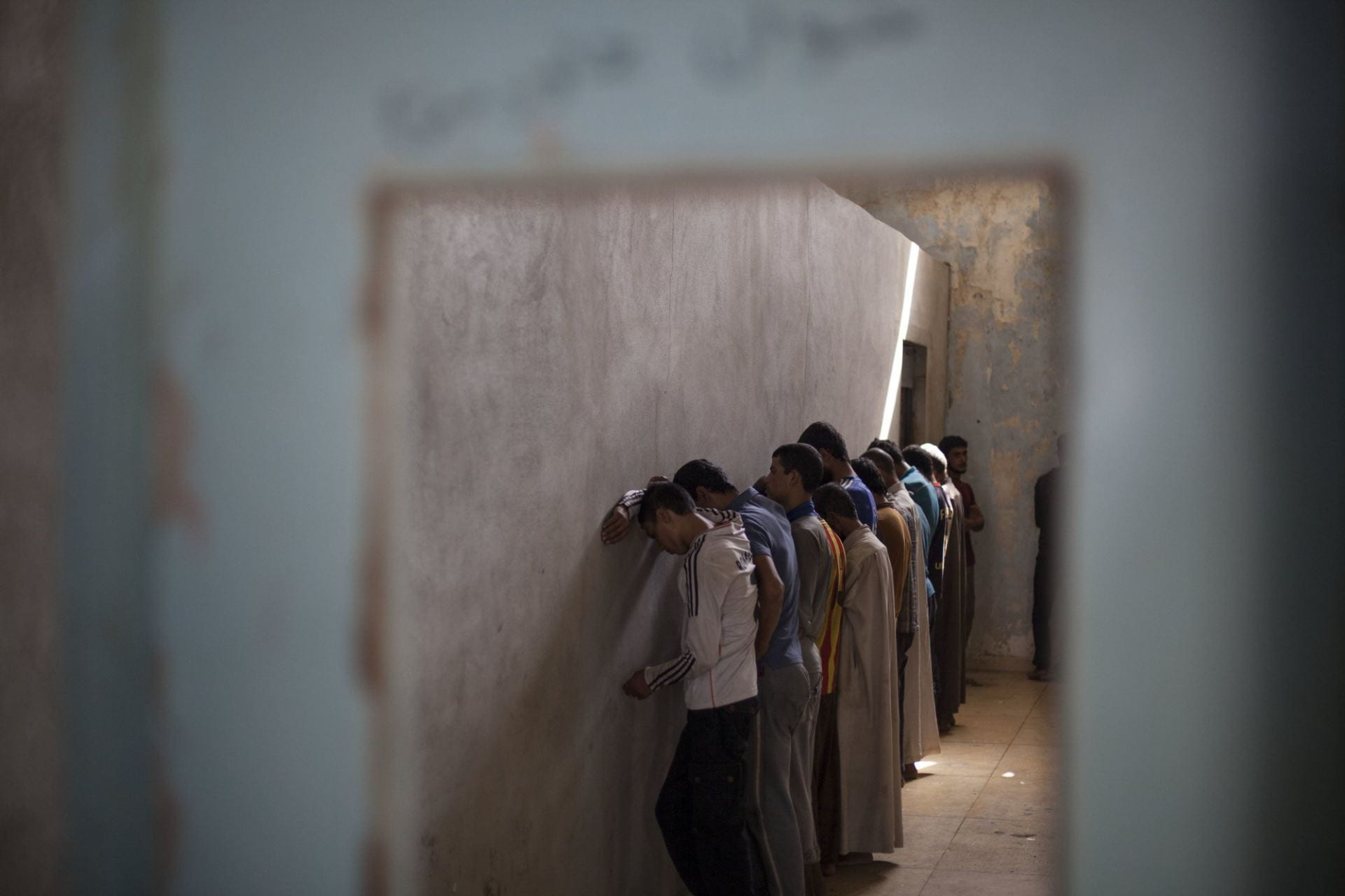 Arrested child suspects line a corridor, awaiting response from the police