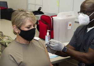 A woman gets her first COVID-19 vaccine