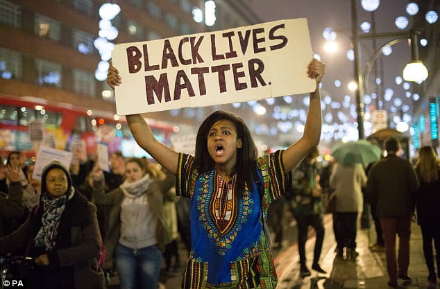 Woman holding a Black Lives Matter sign.
