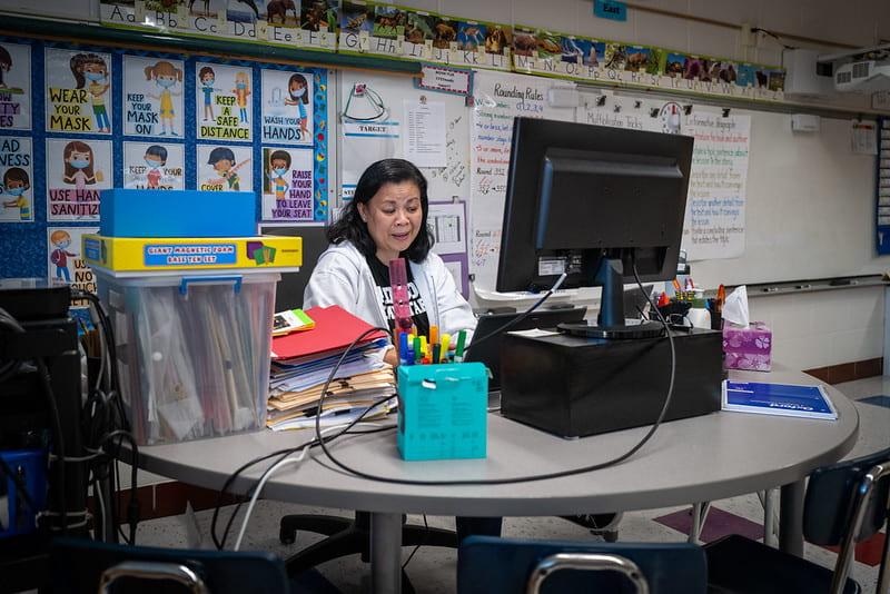 A teacher in an empty classroom teaching online school