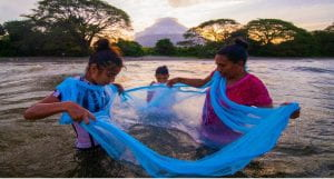 Photo of Nicaraguan mother and daughters fishing with net in river