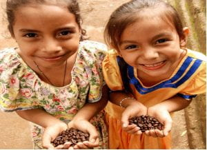 Photo of two little girls holding beans and smiling