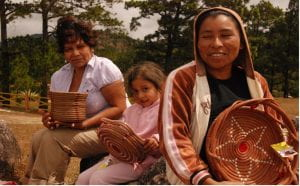 Photo of Nicaraguan women and child holding up woven baskets