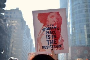"""Yahoo Images, A woman is holding a poster which states """"A woman's place is in the resistance"""""""