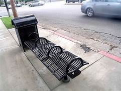 A bench that has armrests in-between to prevent laying down