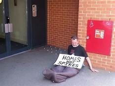 """A person sitting next to a hostile architecture with a sign reading, """"Homes Not Spikes"""""""