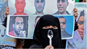 The six prisoners who escaped pictured on a poster with a woman standing with a spoon in support.