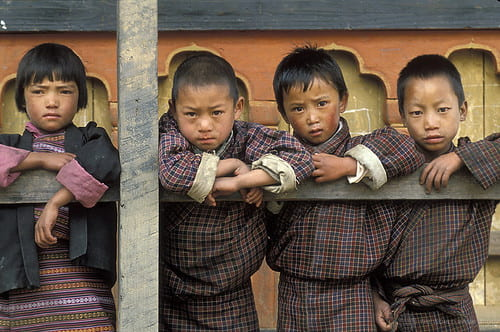 Bhutanese children in traditional attire, leaning over a balcony