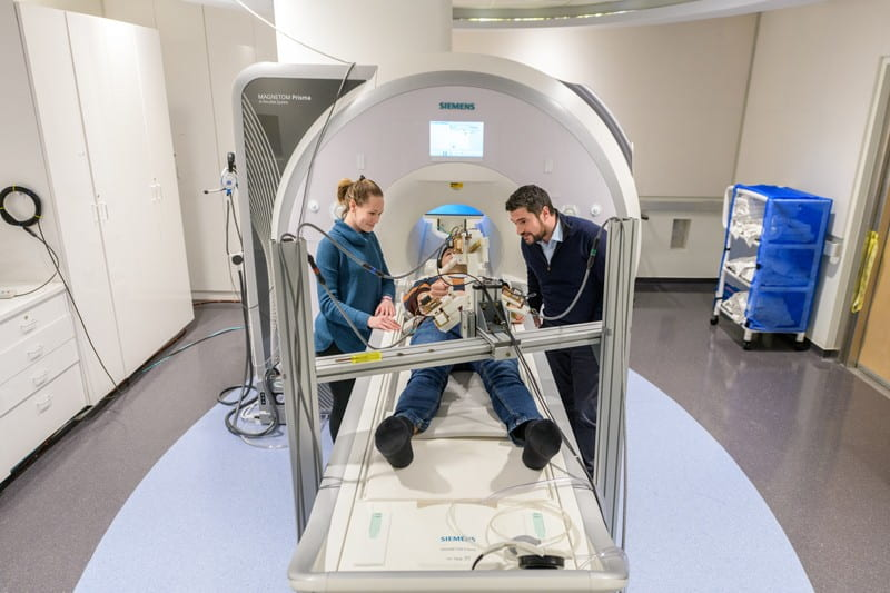 Fabrizio Sergi (right) has created a niche area by developing MRI-compatible robots to study how human brains and muscles work during natural and effortless movements. Many robots used in medical research can't be used with an MRI machine, making it difficult to study brain activity during their use.