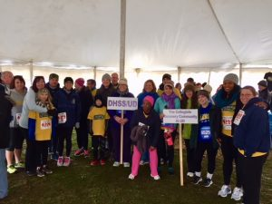 Participants in the 5k stand together under a tent holding signs and smiling.