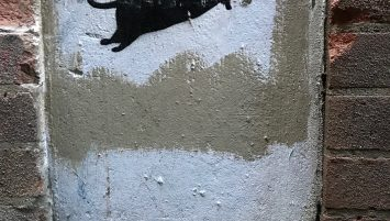 """A black rat stenciled over white painted background on a building. The words """"BLECK LE RAT"""" appear stenciled below."""