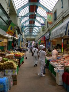 Interior view of market stalls in Brixton Village. Fresh seafood and meat market stalls (right) face the plantains and other produce (left).
