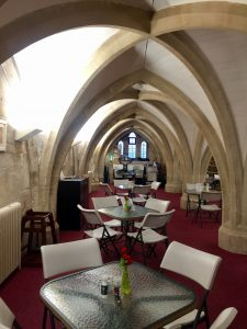 This image shows the interior of St. Mary Redcliffe's Café Arc, filled with modern tables and chairs below the crypt's vaulted ceilings.