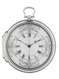 H4 looks like a large pocket watch with a convex glass cover attached to a silver case. The dial is white enamel with blued steel hour and minute indicators and a silver-colored seconds hand. The hours are indicated by Roman numerals within two black circles, and each five minutes is written in Arabic numerals in the next largest circle. Four identical floral scrolling designs decorate the outside of the dial at the top, bottom, far left, and far right.