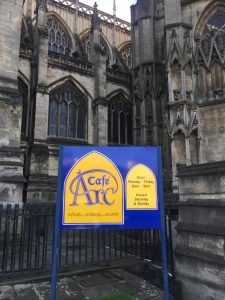 This image shows a close-up view of the front of St. Mary Redcliffe and a colorful sign for the Café Arc, describing its hours of operation.