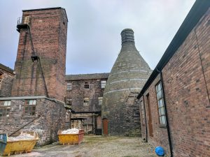 Middleport Pottery's brick bottle kiln standing among several red brick buildings. Two large, metal trash containers filled with recently broken pottery can be see in the left foreground.
