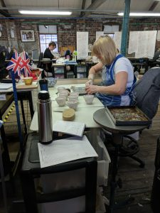 A woman sits at her workbench as she rubs the paper transfer print onto a teacup. She is holding the teacup in her left hand and a bristled brush in her right. Several teacups sit on top of her workbench.