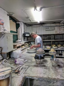 A man stands in front of a spinning stone wheel with his hands on a circular plaster, master mold. A shelf with several plaster molds lines the back wall. On either side of the Middleport employee are molds with pottery in them.