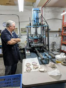 With his arms crossed, a man stares at the sky-blue pad transfer printing machine. The red pad of the machine is pressed against a mini teapot tray. Several other mini teapot trays are on a table in the foreground.