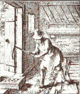Monotone engraving of a man digging saltpeter earth with a large metal pick on a wooden handle. The man wears a hat and has a shovel to the side of his left foot, and the open barn door to his right.