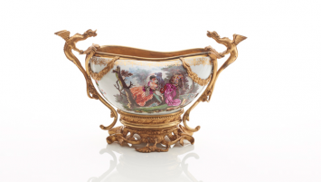 Photograph of Meissen Porcelain Bourdaloue with intricate painted floral decoration and gold dragon mounts. The dragon mounts and gold stand securely hold the porcelain bourdaloue.
