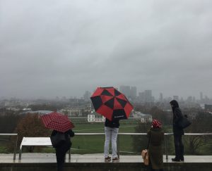 Four individuals look out over Greenwich Park and the London skyline, which is shrouded in fog.