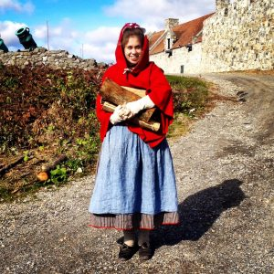 A woman wearing eighteenth-century clothing, including a cloak, stands outside the walls of a stone fort, holding an armload of firewood.