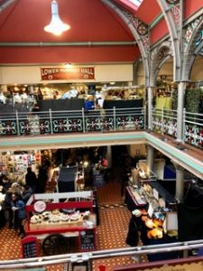 Interior view of Market Hall in Camden Market. Cakes, posters, and silver jewelry are on the first floor.