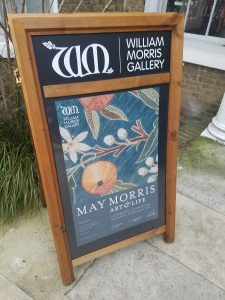A sandwich board museum sign outside the William Morris Gallery in London, England with exhibition information including dates of the show, 7 October 2017-28 January, 2018, and an image of a May Morris embroidery with oranges and white blossoms on branches with multi-colored leaves on a teal green background.