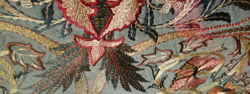 A close up photograph of an embroidered tapestry by May Morris features layered and overlapping scrolling foliate and floral motifs in a range of silk colors with many greens, blues, reds, pinks, and creams on a lighter blue / green woolen background.