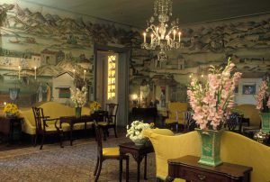 Furniture with yellow slip-covers and upholstery populates a room. The walls are covered in green, hand-painted wallpaper. A chandelier hangs from the ceiling, and fresh flowers sit in vases.