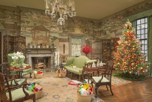 A room with one couch and three chairs, each of which are upholstered in a light green that matches the green of the hand-painted wallpaper. Added to the scene is a Christmas tree with bright multi-colored lights, and four tan baskets with brightly wrapped gifts.