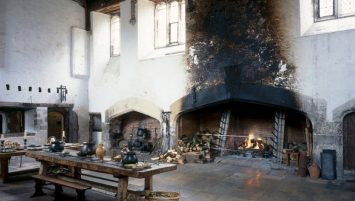 A large fireplace dominates the room, with blackness from fires reaching the ceiling. The blackness stands out against the white walls of the rest of the room. In the foreground sits a long table with cauldrons, bowls, and baskets of fresh vegetables.