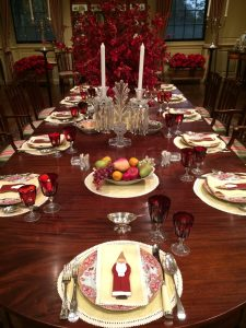 During Winterthur's Yuletide 2017 tour, the du Pont Dining Room table is set with red patterned ceramics and glassware, with a traditional-looking St. Nicholas cookie on the center of each dish, completing the festive atmosphere.