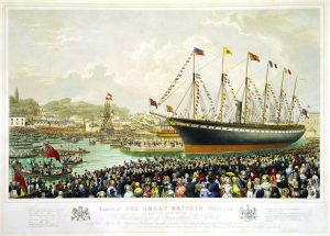A large steamship decked in nautical and national flags sits in a harbor while a sea of onlookers dressed in colorful bonnets and top hats looks on.