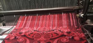 A section of patterned red and black carpet is being produced by a large mechanical loom, which is holding up a row of red and pink threads.