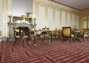 View of the corner of a large room with high ceilings and white walls painted with gilded decorative accents. Empire-style tables and chairs upholstered in yellow fabric stand atop a pink, gray and red carpet with a geometric pattern.